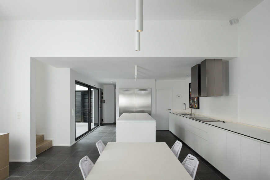 Open dining and kitchen space is awash in pure white with miniature details: black trim on countertops, brushed aluminum cube shaped hood vents, minimalist canister lighting down center of the ceiling.