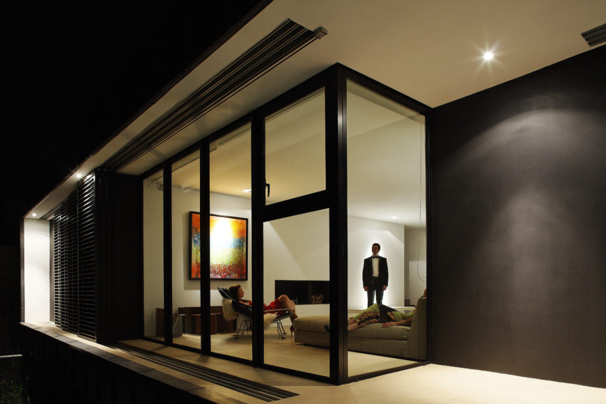As seen from outside, the living room wrapped in glass can be completely obscured by sliding shutter panels.