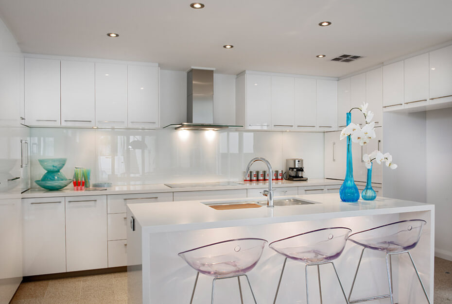 A trio of transparent bar style chairs line up at the large glossy-white island with built-in sink in this kitchen, outfitted with a broad swath of white cabinetry and backsplash with metallic hardware.