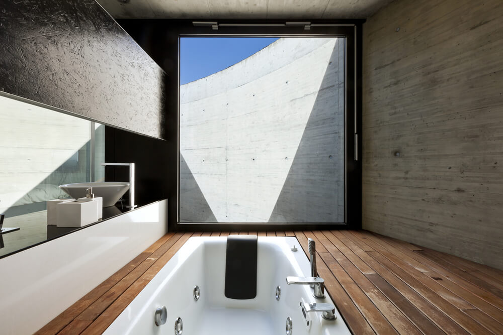 Textured, minimalist bathroom centers natural hardwood raised platform around bathtub in this separated space set against floor to ceiling window. Vanity in black and white stands at left.