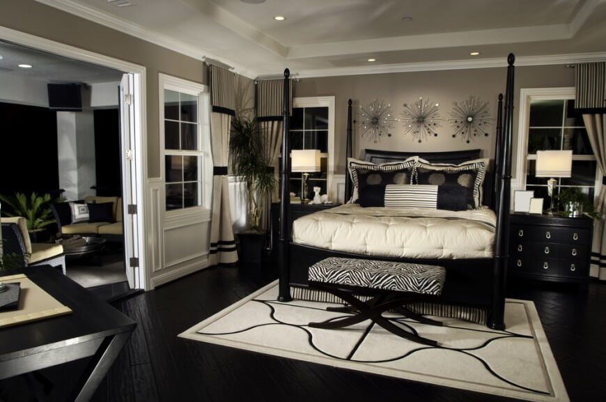 Beautiful bedroom with zebra print ottoman at the foot of the bed