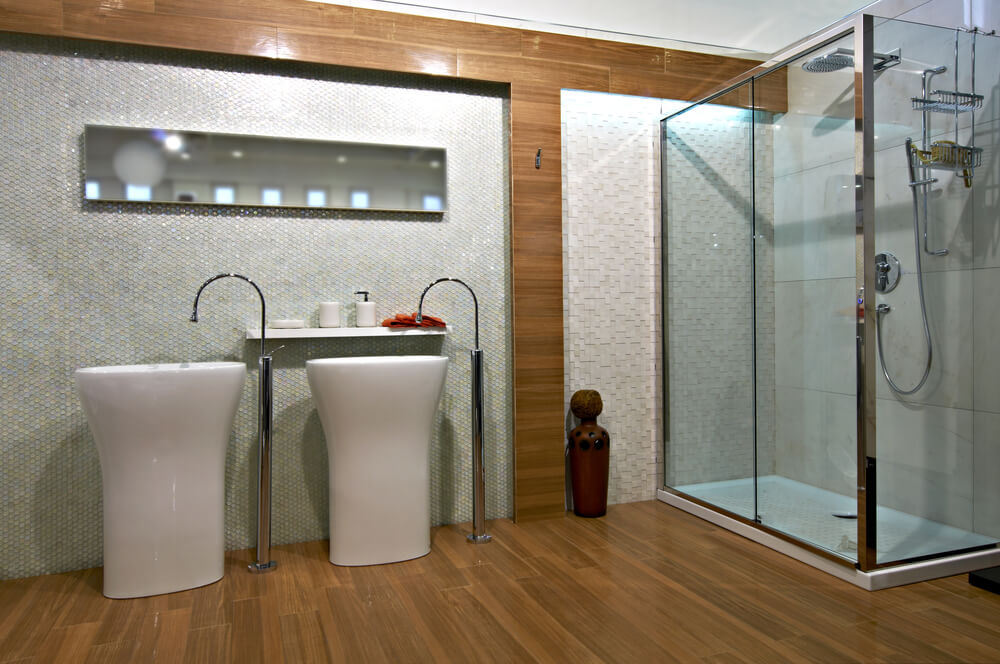Ultra modern appointments in this bathroom feature floor mounted faucets paired with pedestal sinks, glass and steel shower structure, and micro-tile wall details in a space filled with natural wood.