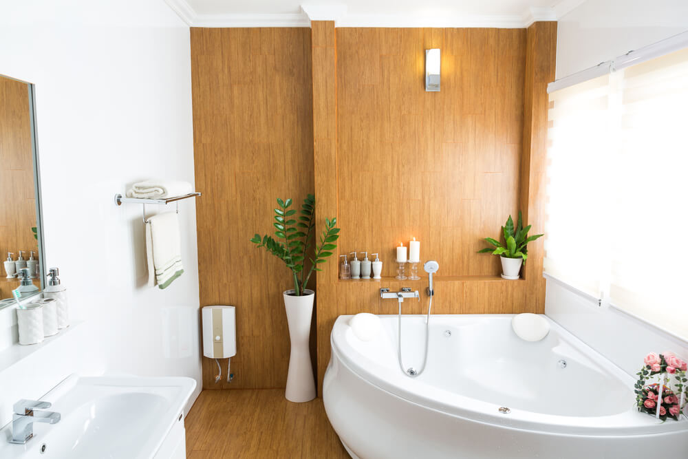 High contrast master bathroom features mixture of natural hardwood and pristine white. Flooring and detail wall in wood pair with large corner jacuzzi tub and vanity in white.