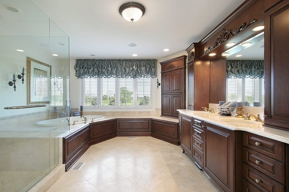 Lengthy U-shaped bathroom fits a sunken corner tub and all-glass shower across from full height dual vanity with dark wood cabinetry. Rounded tub surround features matching wood panels.