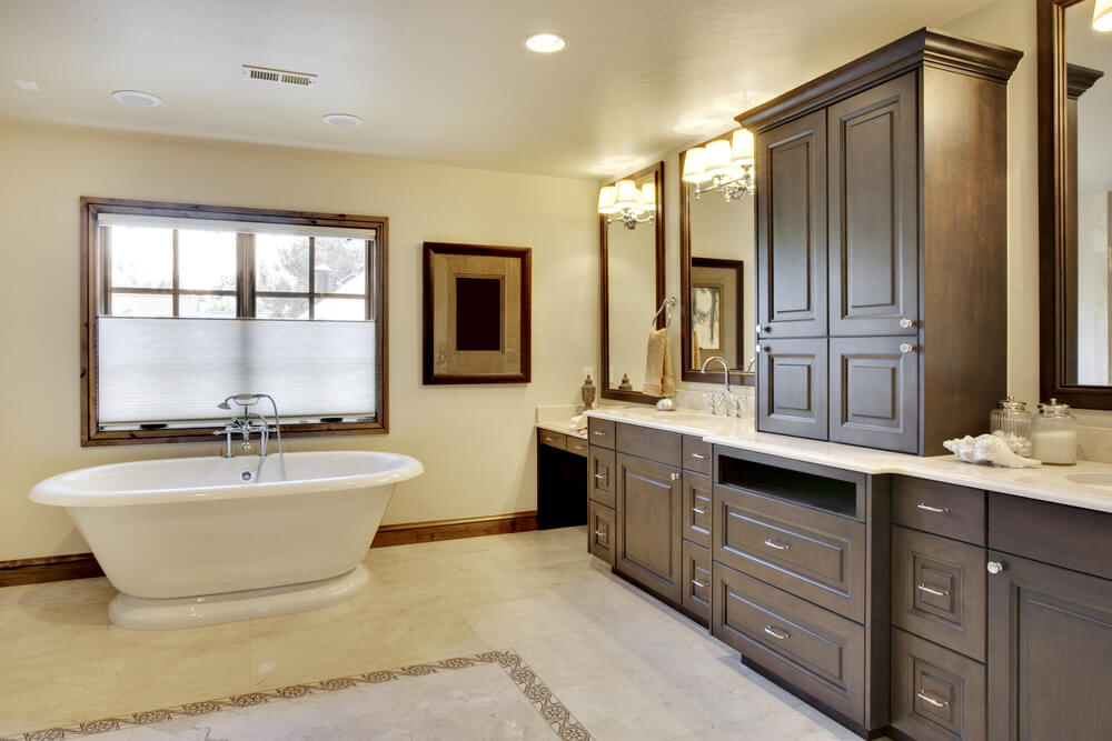 Large bathroom stands a white pedestal tub across expanse of patterned tile flooring from wall-length dark wood vanity, including dual sinks, upper cabinetry, and lowered powder section.