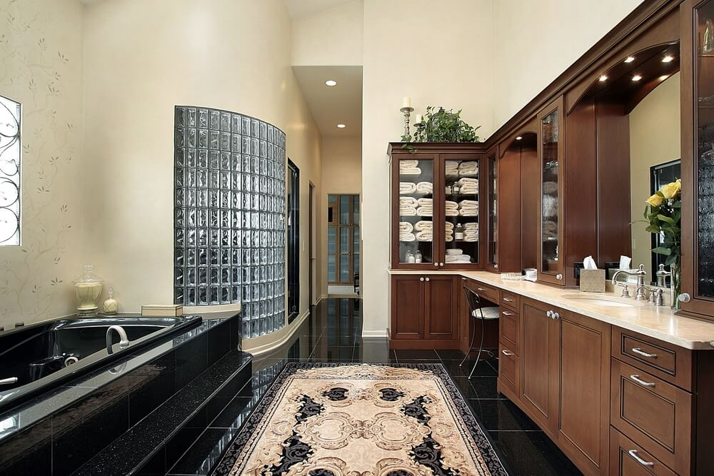 Large, opulent bathroom is populated with a variety of textures and tones, from black marble flooring and tub surround, to glass brick shower wall, to dark wood vanity. Array of glass-door cabinets stand above beige marble countertops between vanity mirrors.