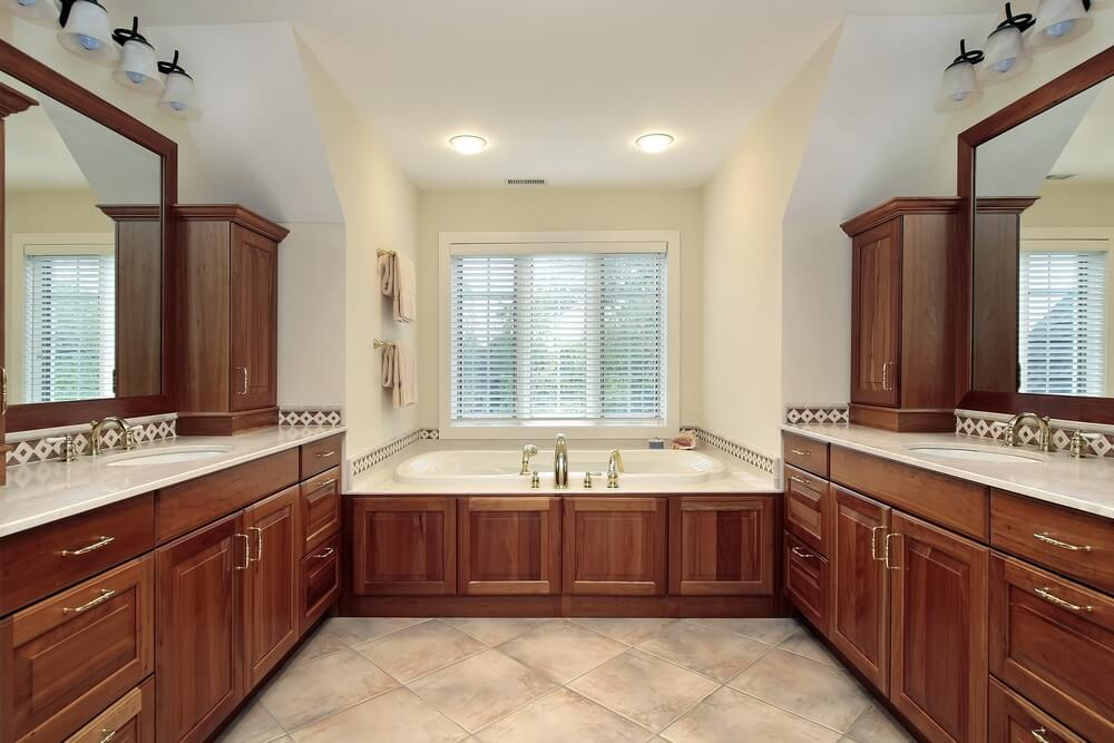 Symmetrical bathroom holds twin warm toned wood vanities facing each other over matching wood wrapped, window seat bathtub.
