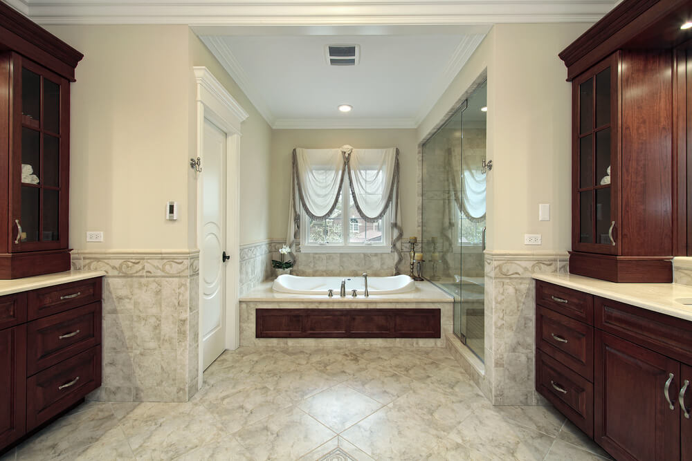Luxurious master bath is awash in patterned marble, with twin large vanities in dark wood tones and white marble countertops, plus large all-glass walk in shower and bathtub surround with matching wood panel.
