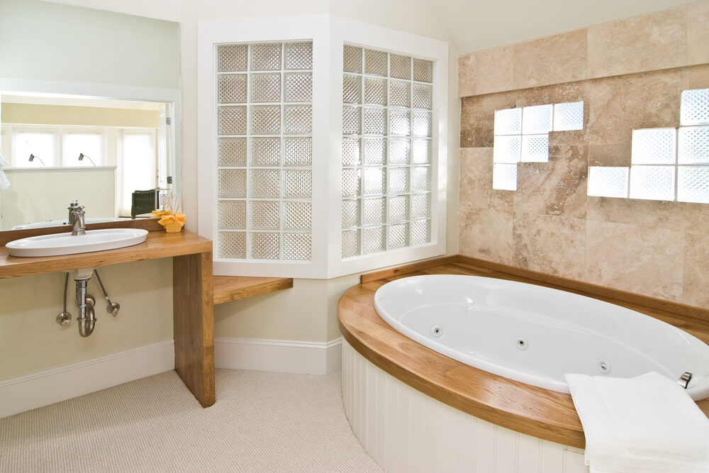 Bathroom making novel use of textured glass bricks, embedded in tile and white wood, above natural wood bath frame and vanity.