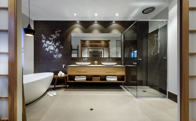 View into the primary bath reveals natural wood vanity with twin vessel sinks, pure glass walk in shower, and detailed view of the delicate floral print on dark mirror mounted wall.