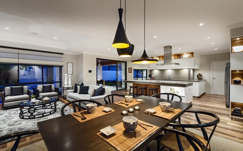 Angled view over dark wood dining table highlights the relaxed, grey toned living room space at left, black contemporary chandeliers overhead, and immense open flow.