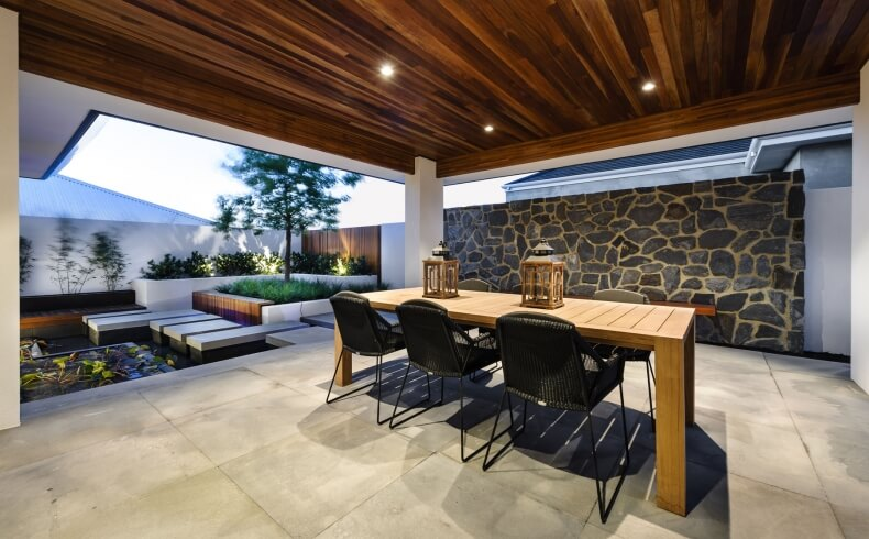 "Patio space heightens the Zen garden feel, with ""floating"" stone platforms surrounding a small pool, white concrete walls supporting corner manicured garden, and more of the ceiling timber overhead protected dining space."