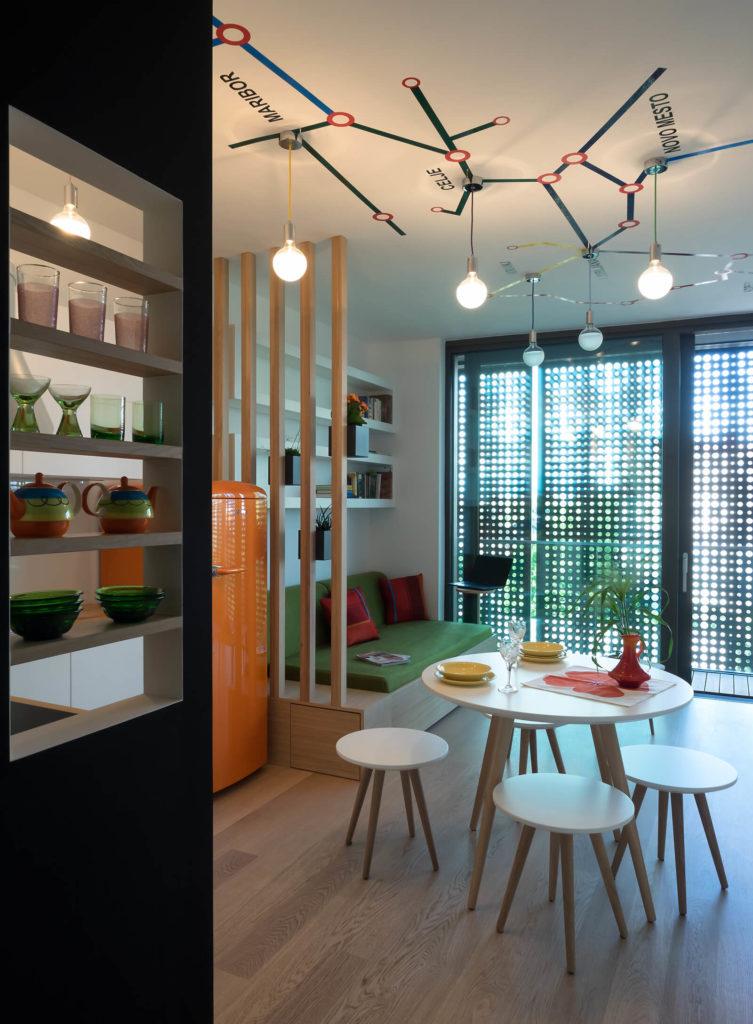 With black dividing wall at left, we see the kitchen integrating with the living room, exemplified by the bold orange refrigerator standing next to natural wood framed sofa with green cushion. Above we see the train station map.