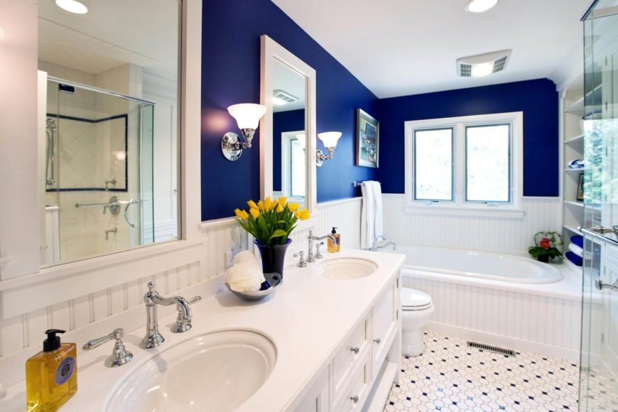 Striking blue and white scheme frames this cozy bathroom, with white dual vanity flanked by chrome wall sconces. Large whirlpool tub sits below windows at far end, with all-glass shower at right.
