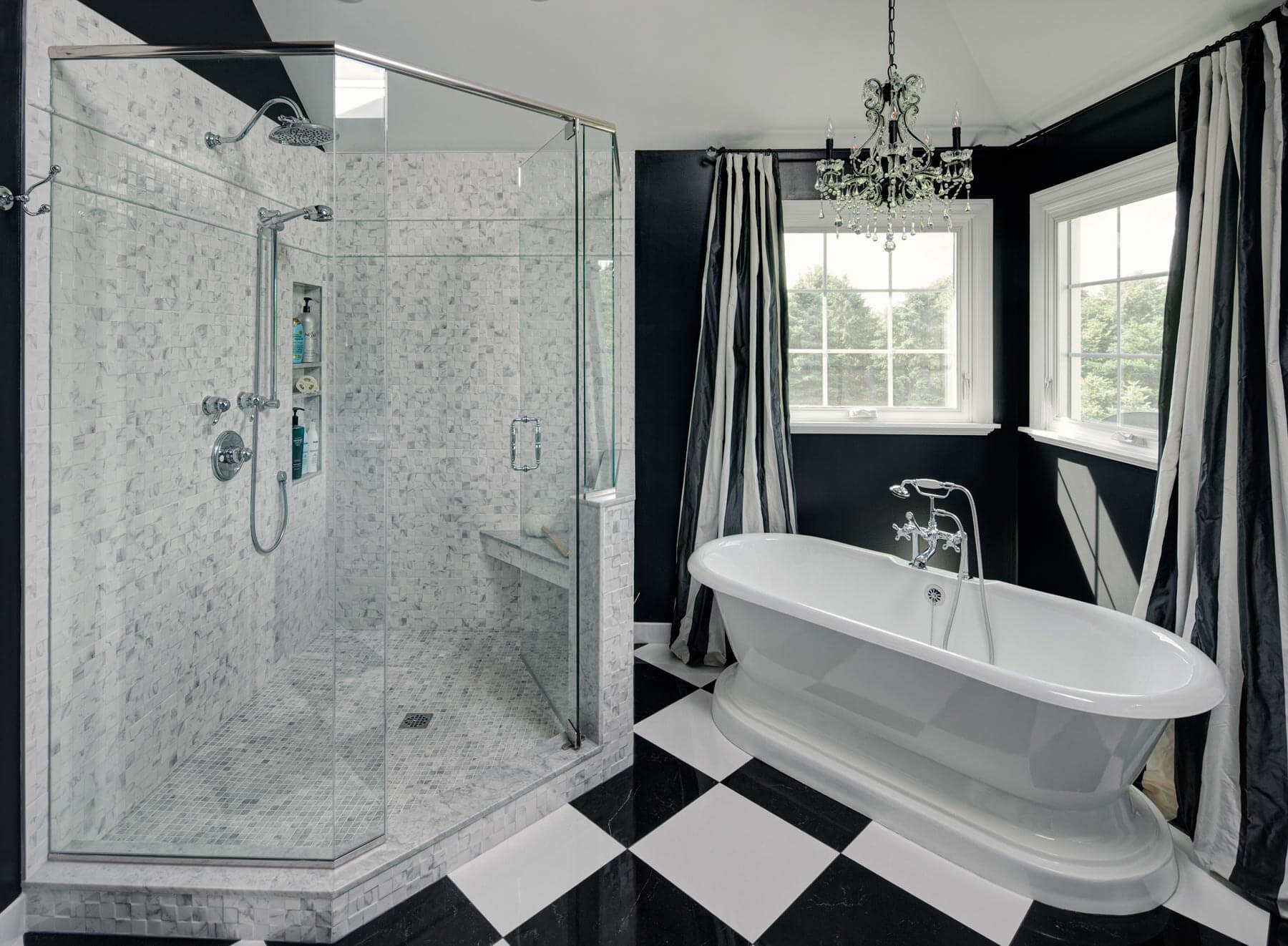 Immense glass shower is wrapped in diffuse tiling, next to an elegant free standing soaking tub. A pair of windows and chandelier in this corner adds a touch of inviting charm to the bathing space.