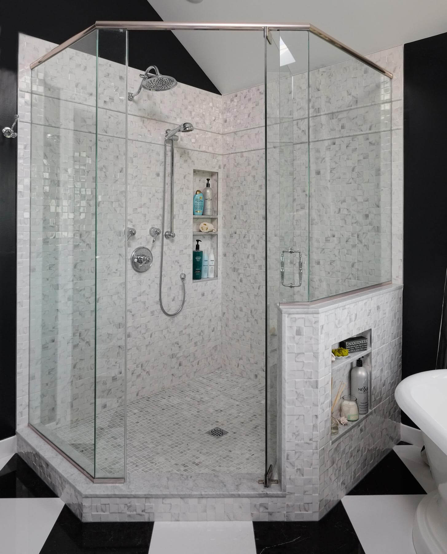 The tile shower structure holds built-in shelving within and outside the glass enclosure. Chromed hardware and faucets assist in the elegant look.