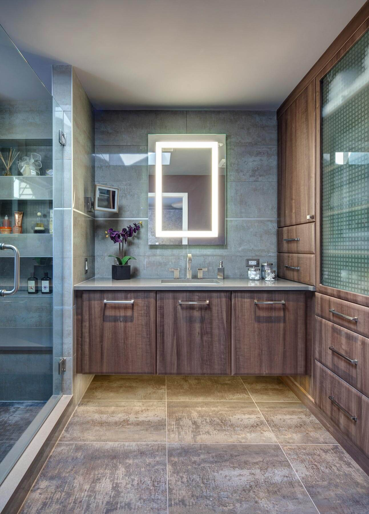 Bathroom features large format natural colored materials and a vanity mirror with internal lighting. A palate of soothing brown and blues were utilized throughout this newly remodeled master bath, while functionality was added via an array of shower shelving and cabinetry.