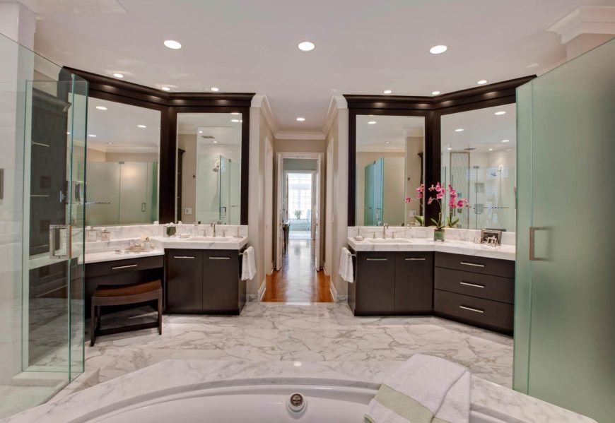 "Espresso cherry wood cabinetry and thick slab countertops define a set of ""his and hers"" vanities flanking this expansive bathroom, replete with marble everywhere. All glass shower stalls stand aside the large jacuzzi style tub at center."
