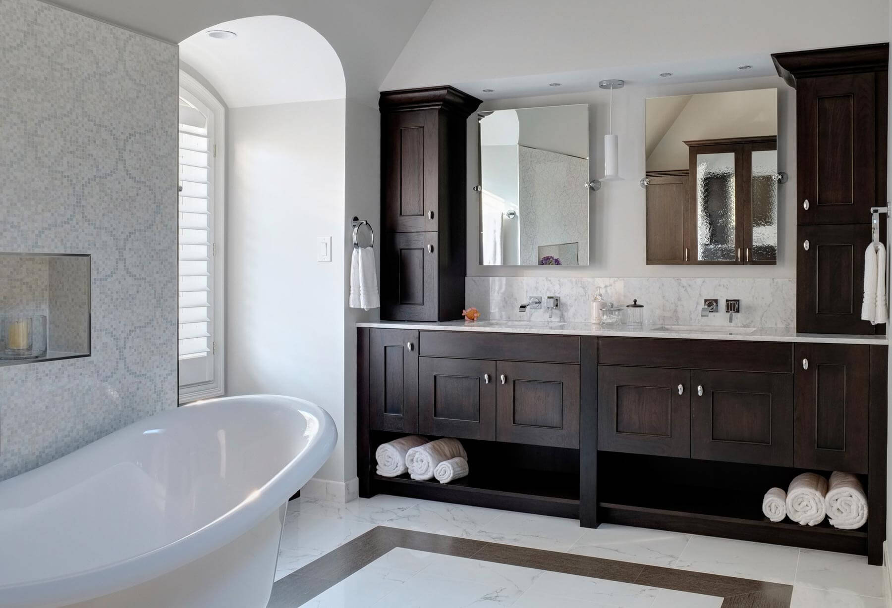 The contrast between dark hickory cabinetry and bright marble defines this large, open bathroom. Mosaic tile wall stands next to white pedestal tub, while dual vanity with tilting mirrors floats above marble backsplash.