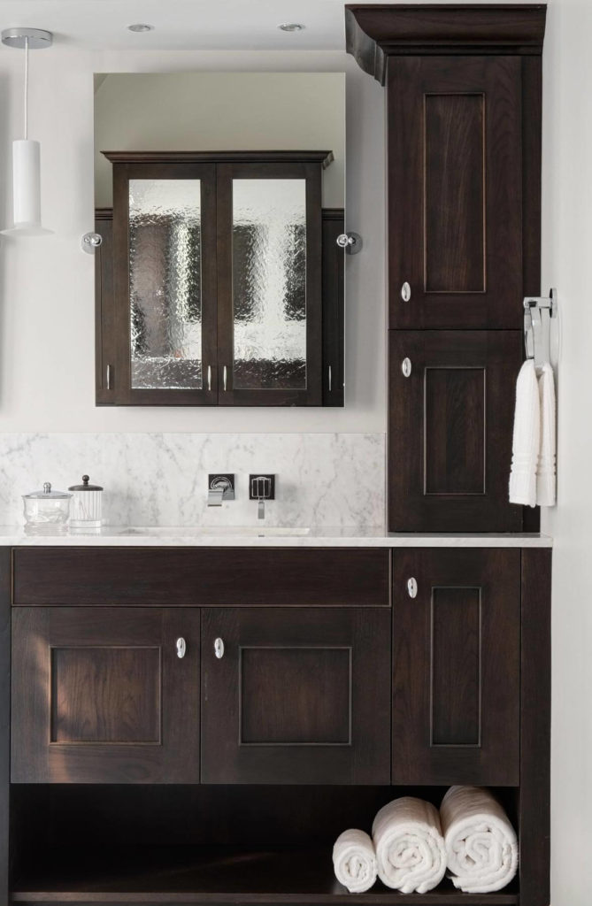 Vanity features marble countertops reaching up for a 9 inch backsplash, holding wall mounted faucets below pivoting mirrors.