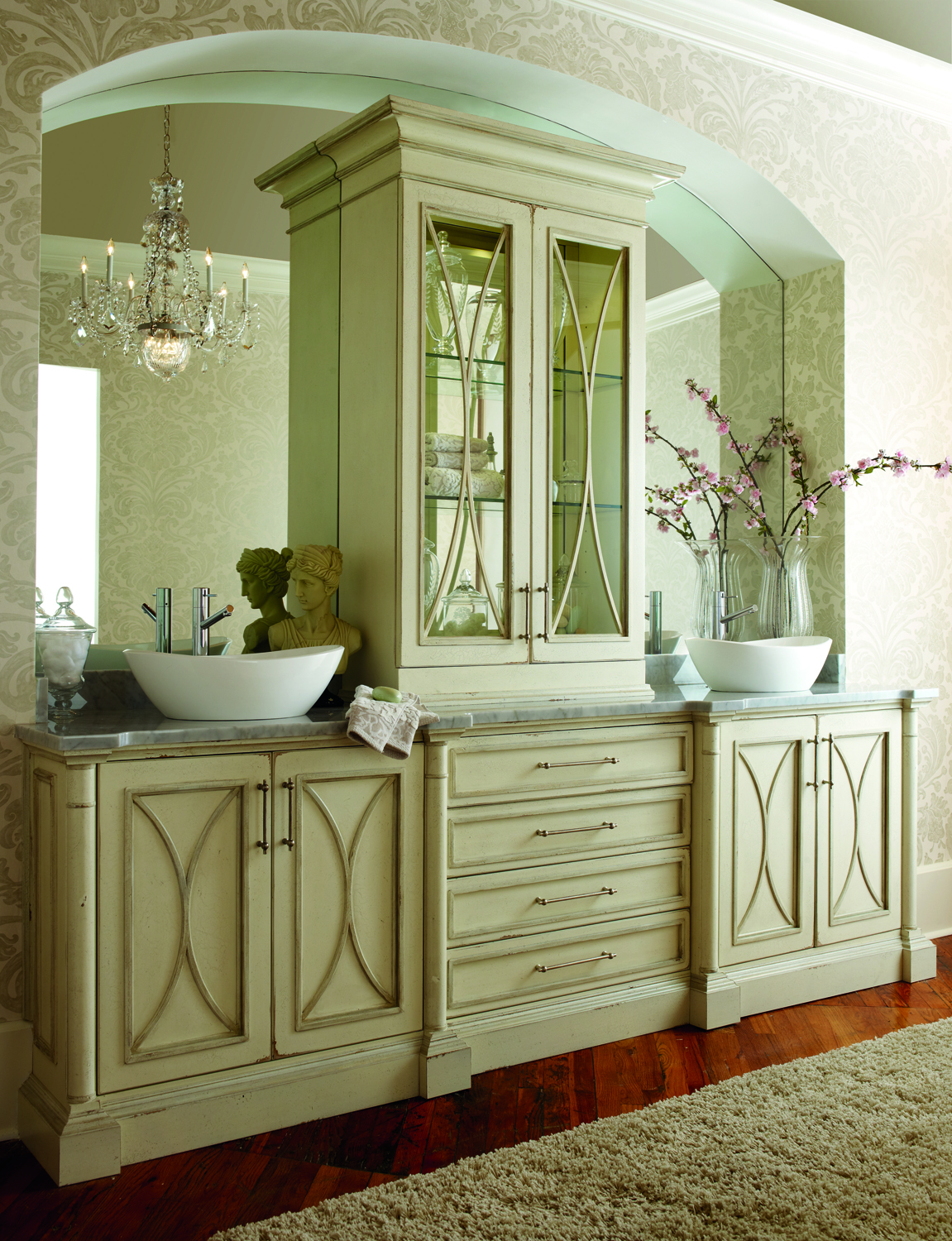 Habersham Cabinetry designed this gorgeous dual vanity with treated wood cabinetry, white vessel sinks, and marble countertop. Glass door cabinet divides the massive single wall mounted mirror at center.