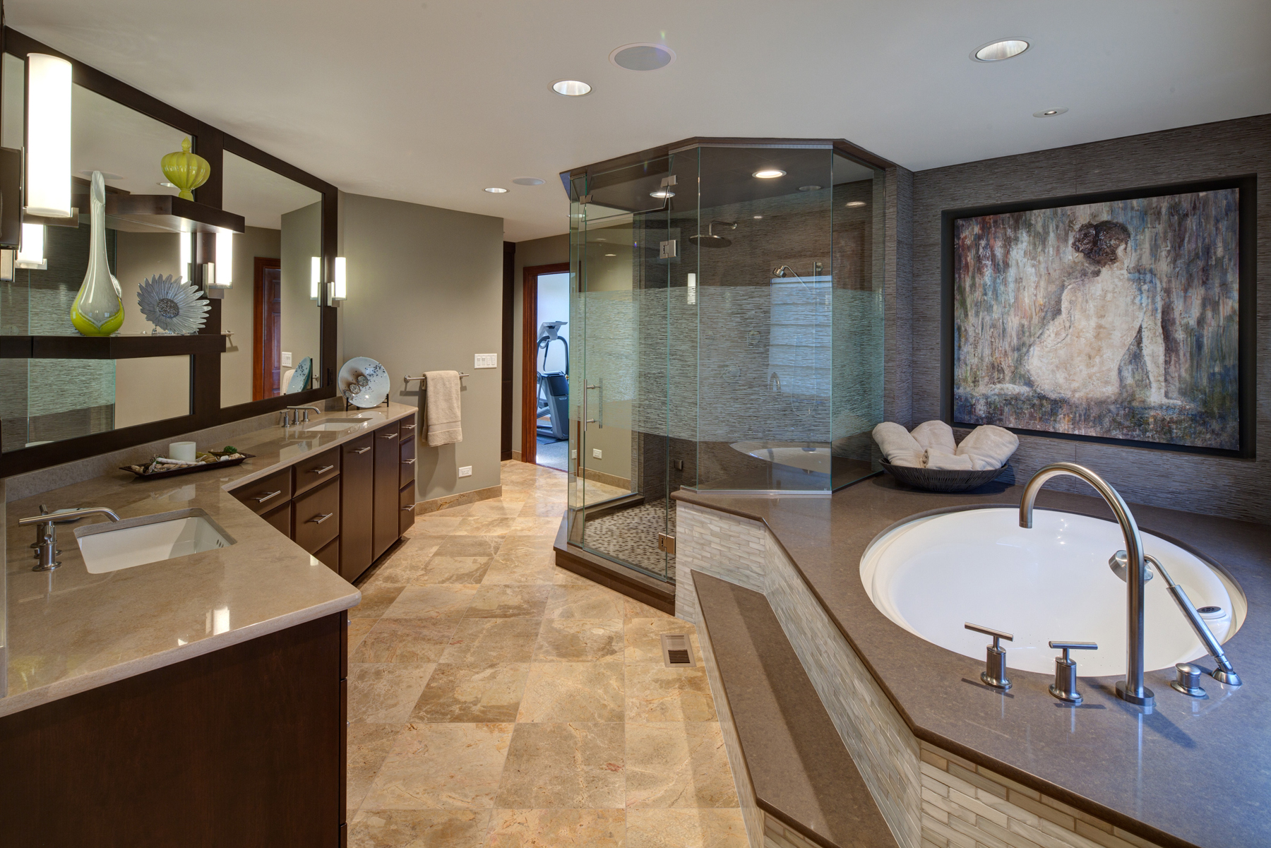 This lavish oasis of a bathroom stands a large etched glass shower at center, with recessed bath niche at right and lengthy vanity at left. Mirrors hold both custom shelving built into the surface, and a hidden television behind one of the panels. Homeowner's artwork is displayed on niche wall.