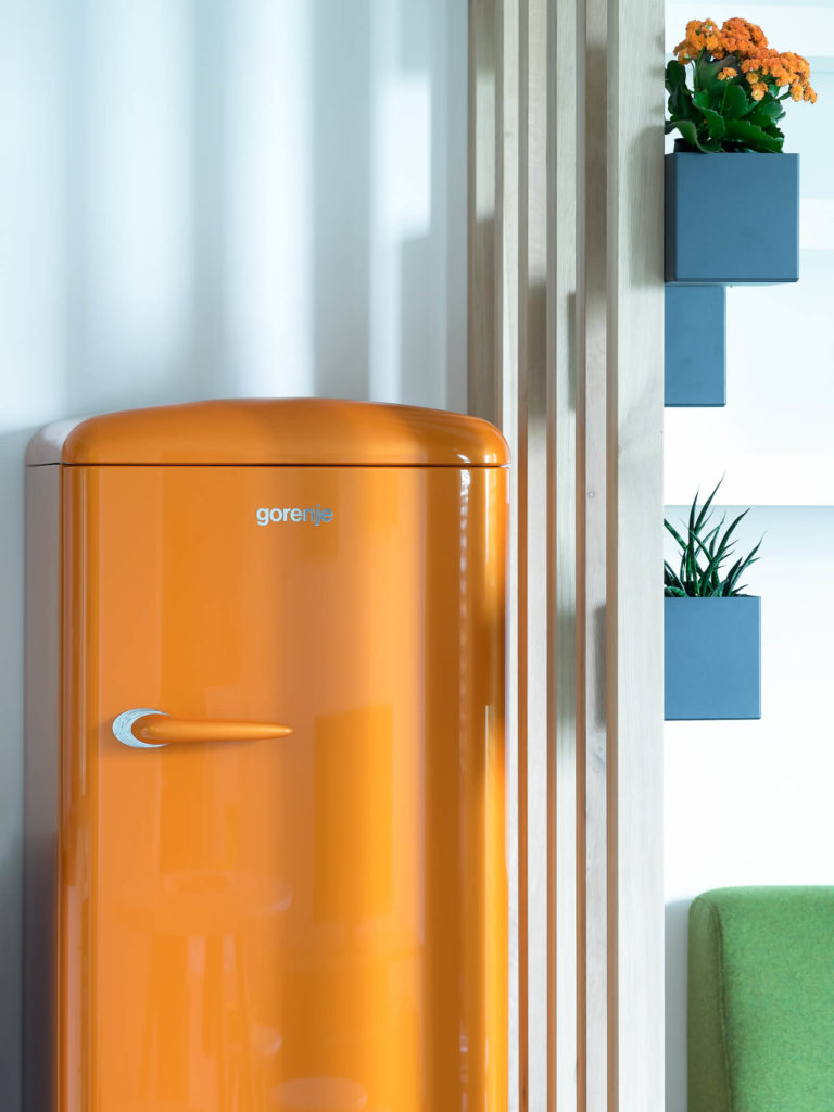 The bold orange refrigerator is one of several bright splashes of color bursting from the neutral toned interior. Blue potters are seen hanging from the natural wood dividing wall above the green sofa.
