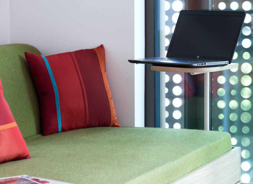 Beside the sofa, we see a small laptop platform, in white metal and natural wood.
