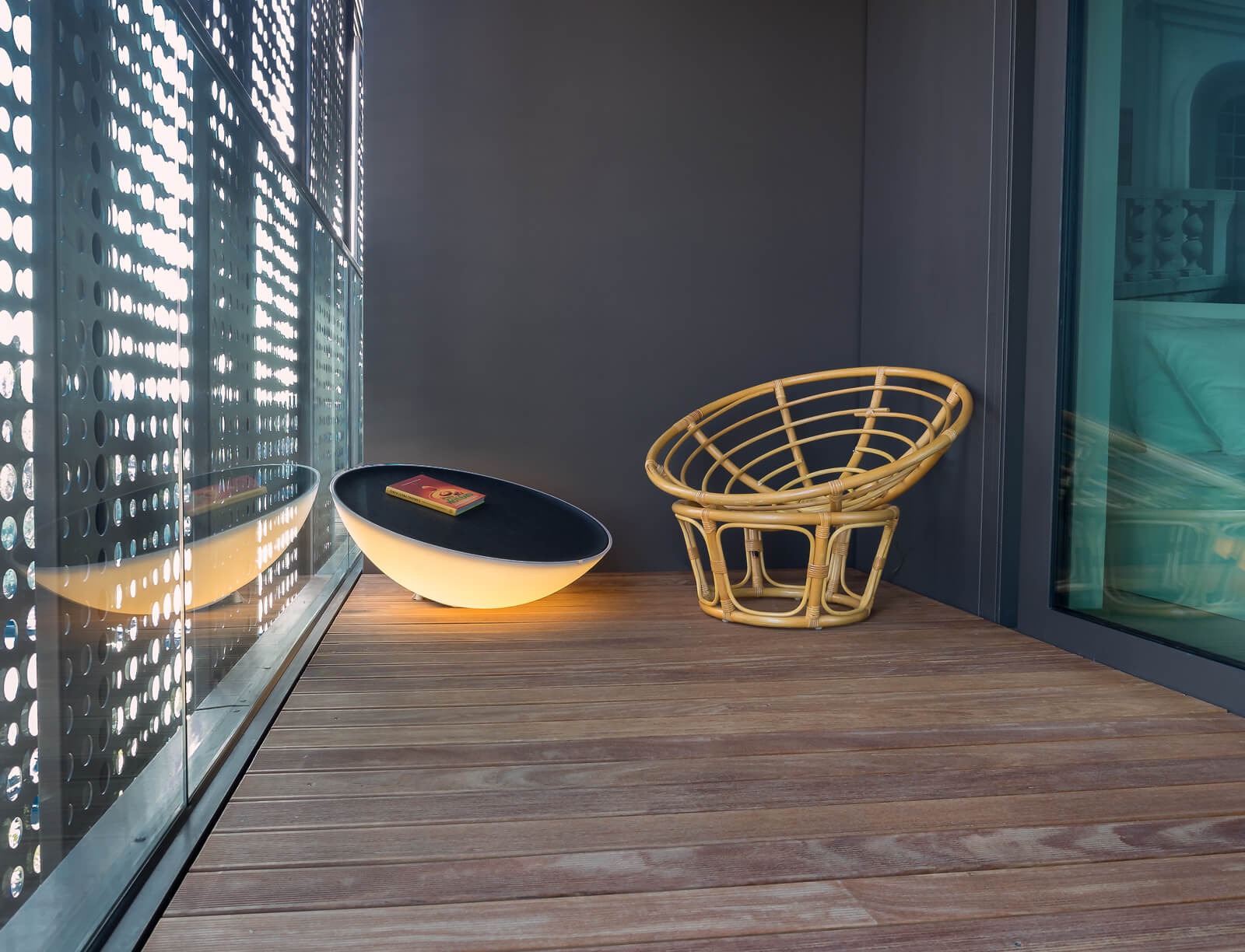 On the bedroom patio space, we see this thoughtful combination of a wicker chair and hemispherical table lit from within.
