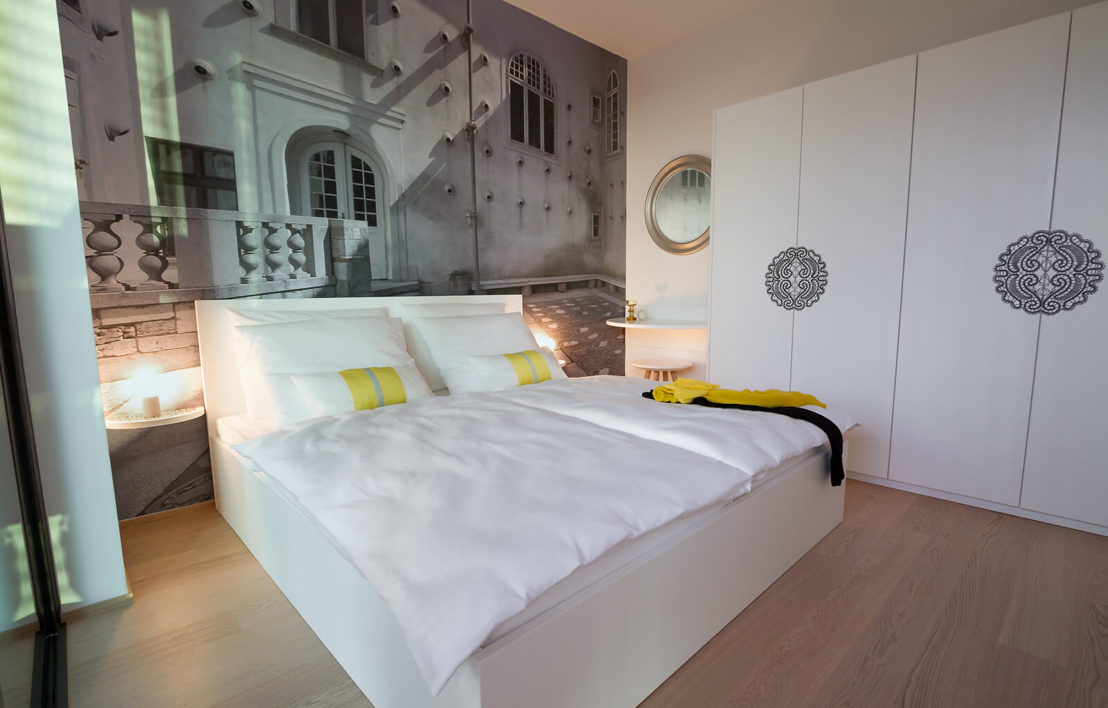 Small lighting shelves flank the bed, while white closet doors stand across, with art printed doors.