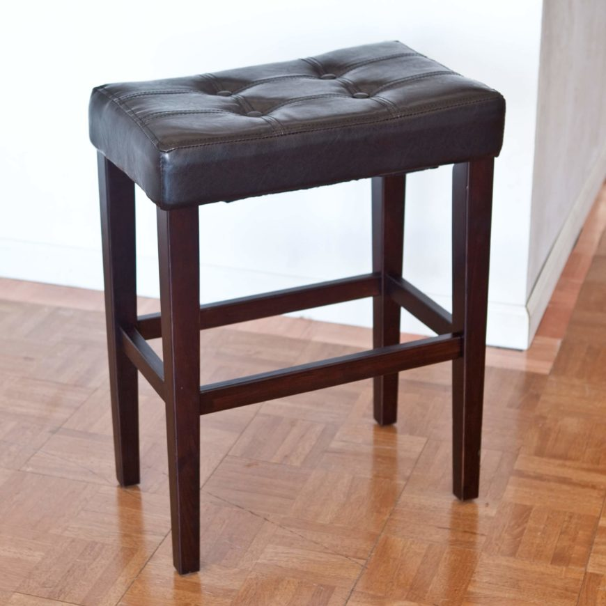 Basic saddle style stool with wood legs and black upholstered seat.