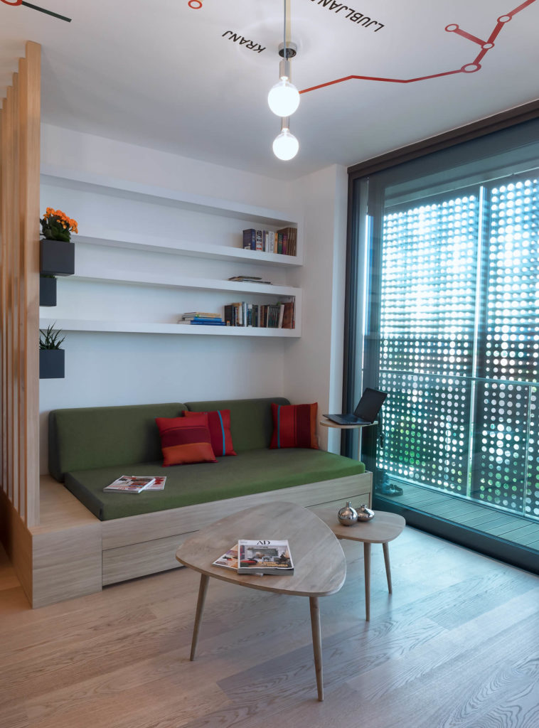 The built-in green cushioned sofa conceals storage space within the natural wood frame. Built-in white wall shelving sits overhead.