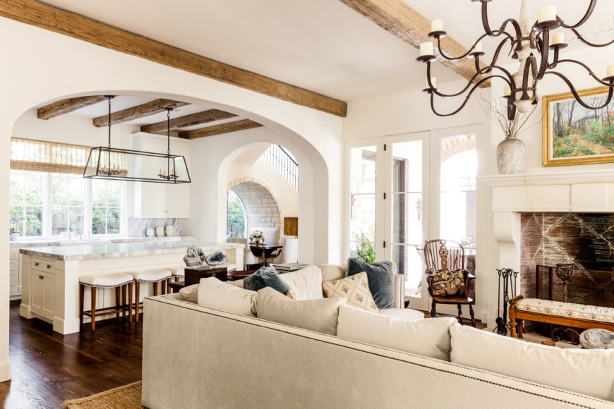 Exposed ceiling beams can be seen throughout this part of the home, adding a sense of old fashioned charm to the bright white luxury. The kitchen, with massive marble topped island, can be seen at left.