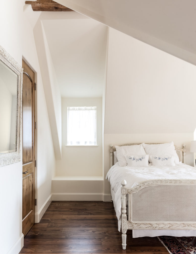 This room features another white painted bed frame, contrasting with rich hardwood flooring.