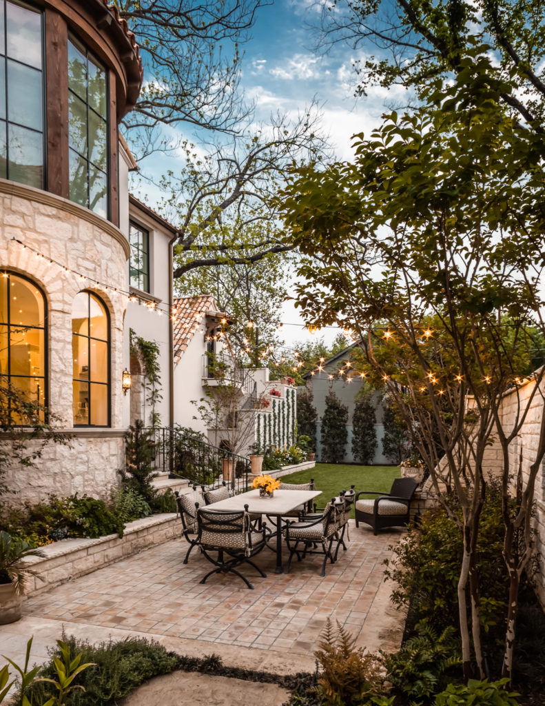 The outdoor relaxation space extends beyond the covered areas, including this brick patio at the center of a small courtyard. Greenery surrounds every wall, making for close communion with nature.