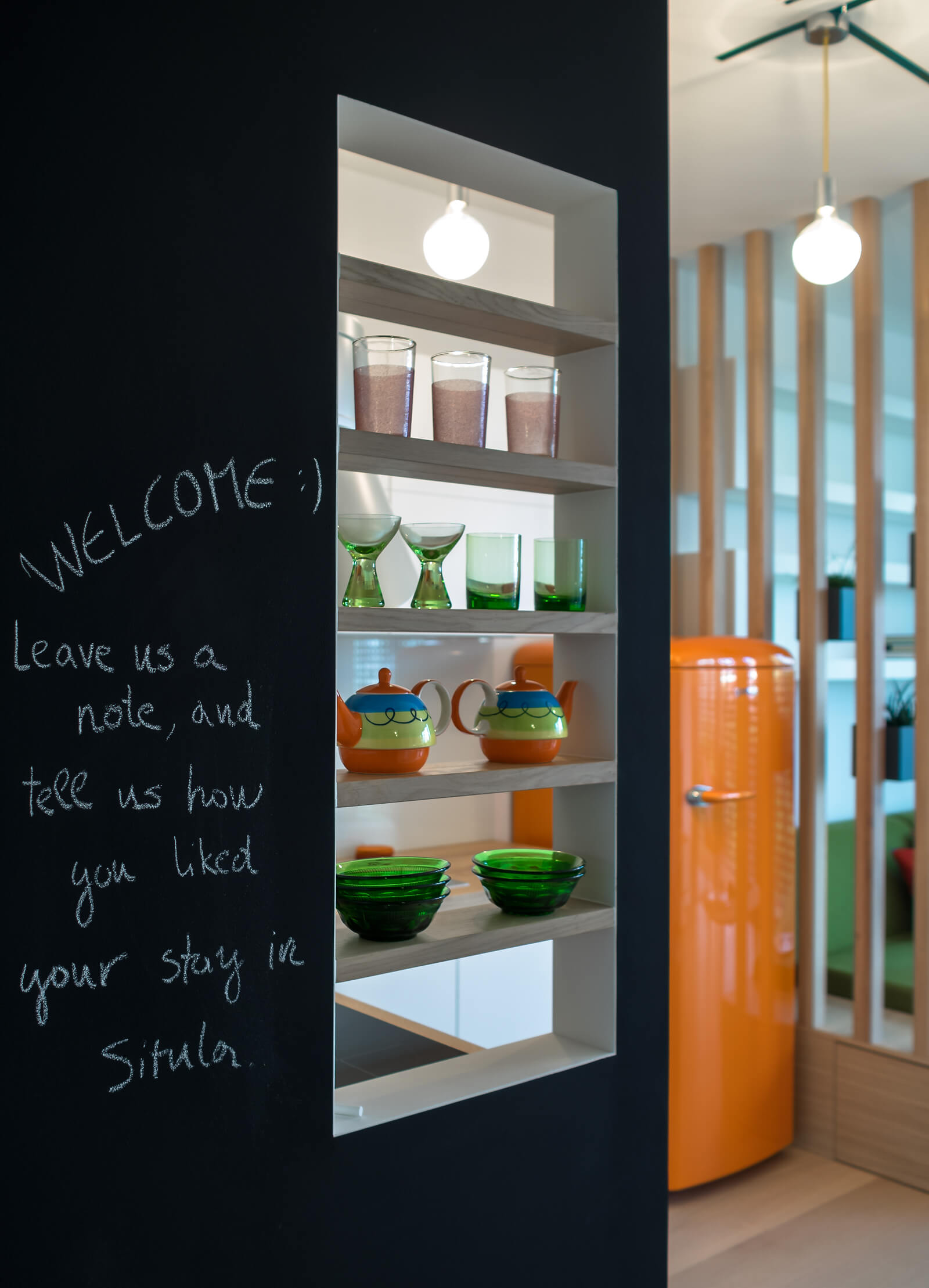 Here we see a close view of the kitchen dividing wall, covered in chalkboard material so that guests may leave messages. Built-in shelving provides space for decoration.