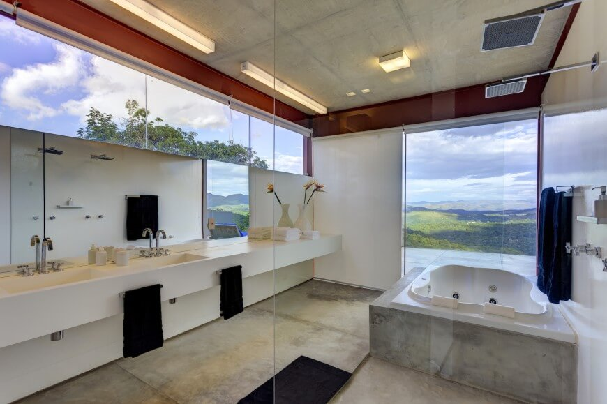 the bathroom as seen looking outward concrete framed jacuzzi tub stands beside floor to ceiling