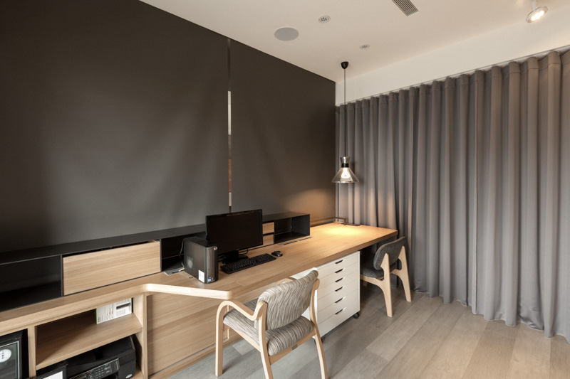 With the dividing curtain and dark grey shades pull down over the lengthy natural wood desk, the office is a fully partitioned private area within the home.
