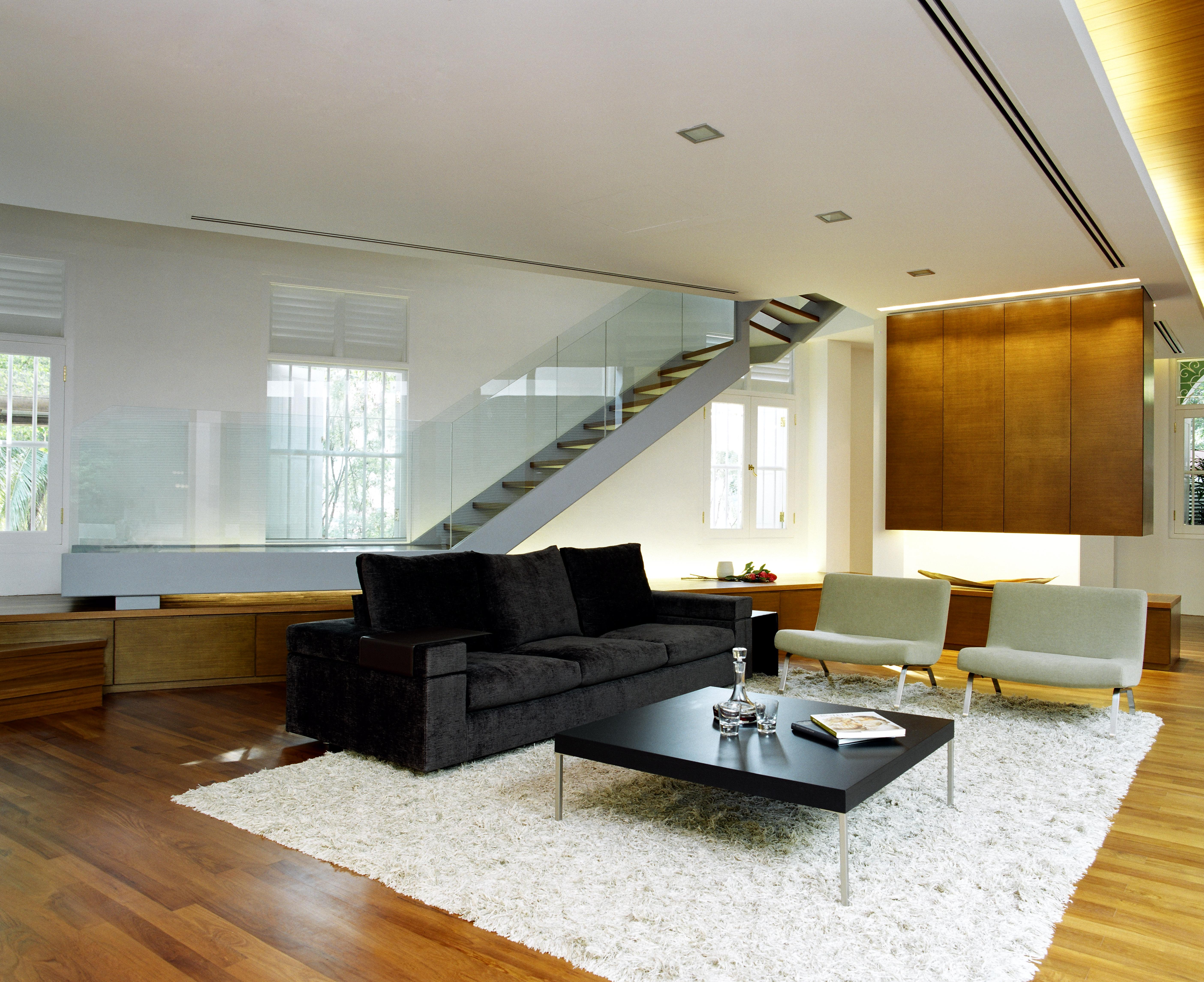 The living room is surrounded by a raised wood platform concealing storage, and acting as a landing for the metal and glass staircase with floating natural wood steps.