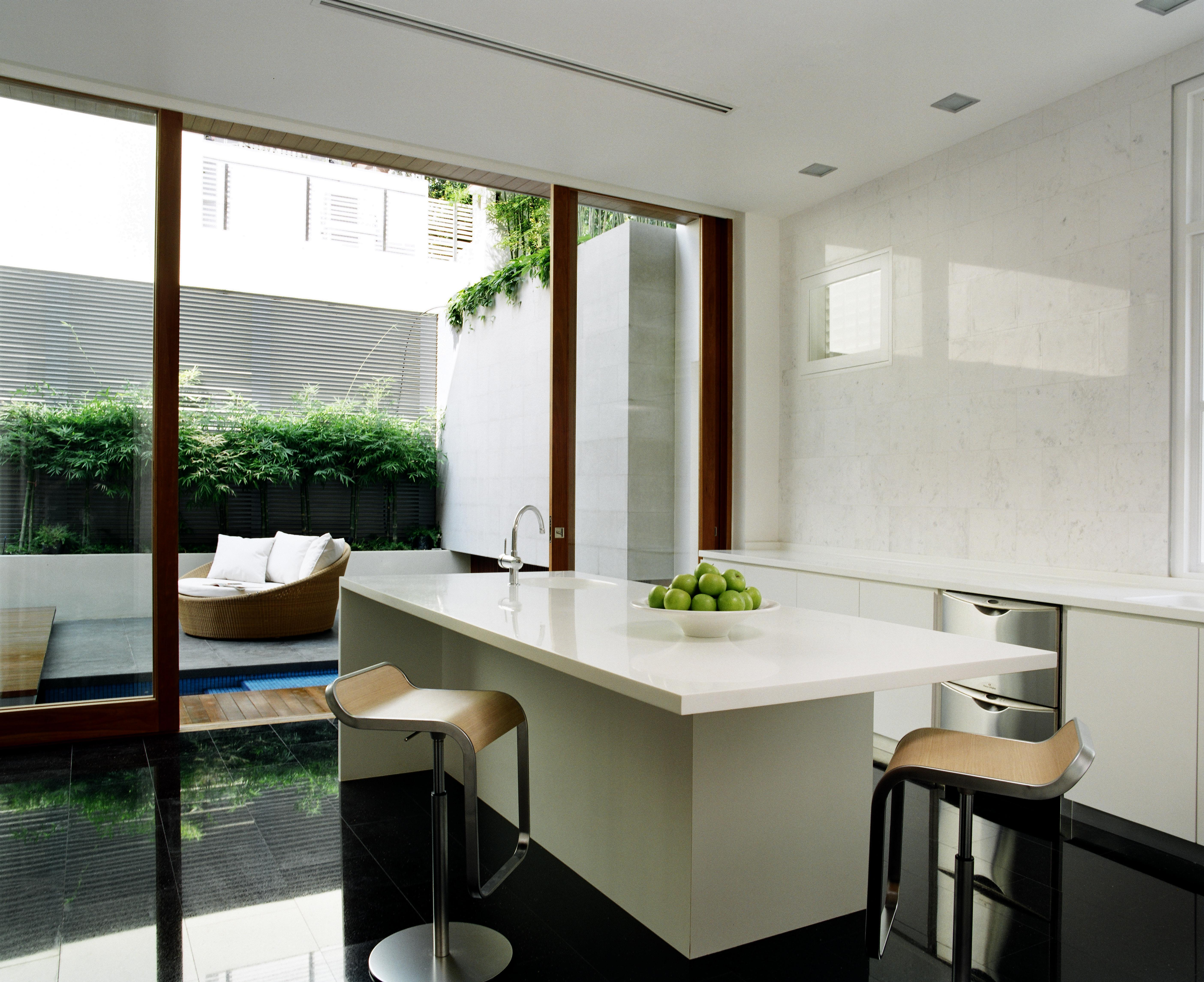 The cozy, minimalist kitchen space is defined by the contrast between black tile flooring and white countertops. Island features dining space over a pair of metal and good stools, while the patio with circular wicker seating is seen through sliding glass panel.