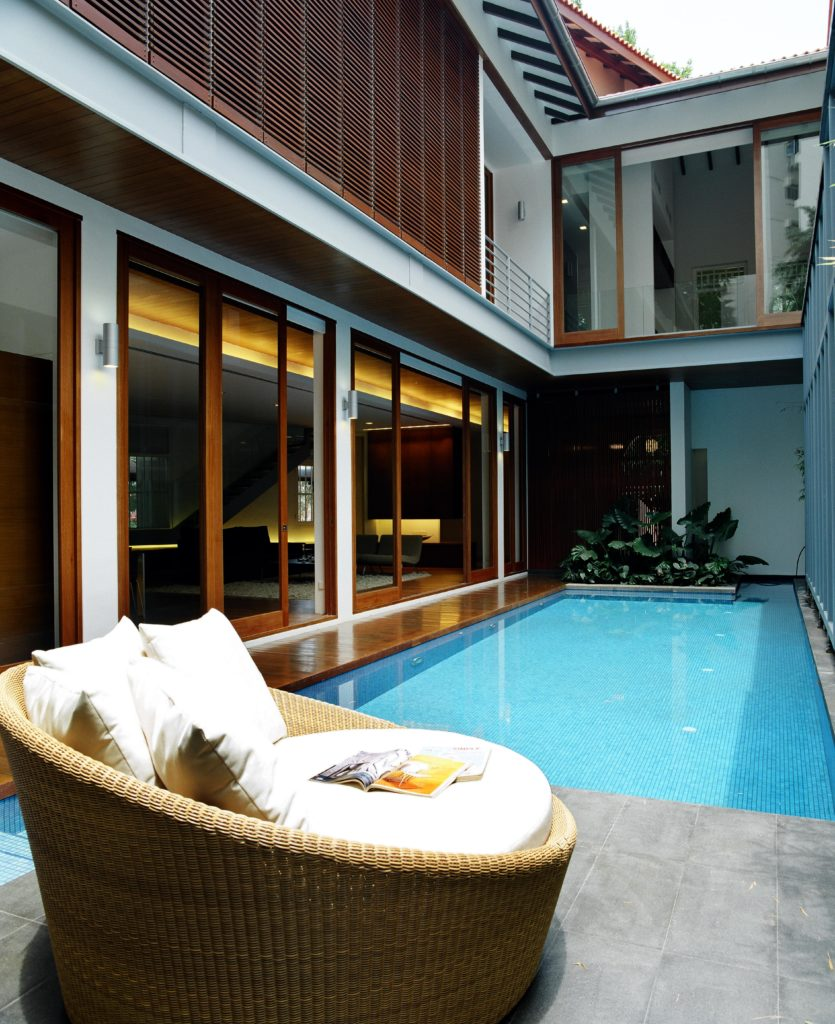 Concrete tile patio overlooks the pool and hardwood surround leading into the living room. Small garden is seen at the far end, near the front entrance, while wooden louvers are seen above, shading the bedrooms.