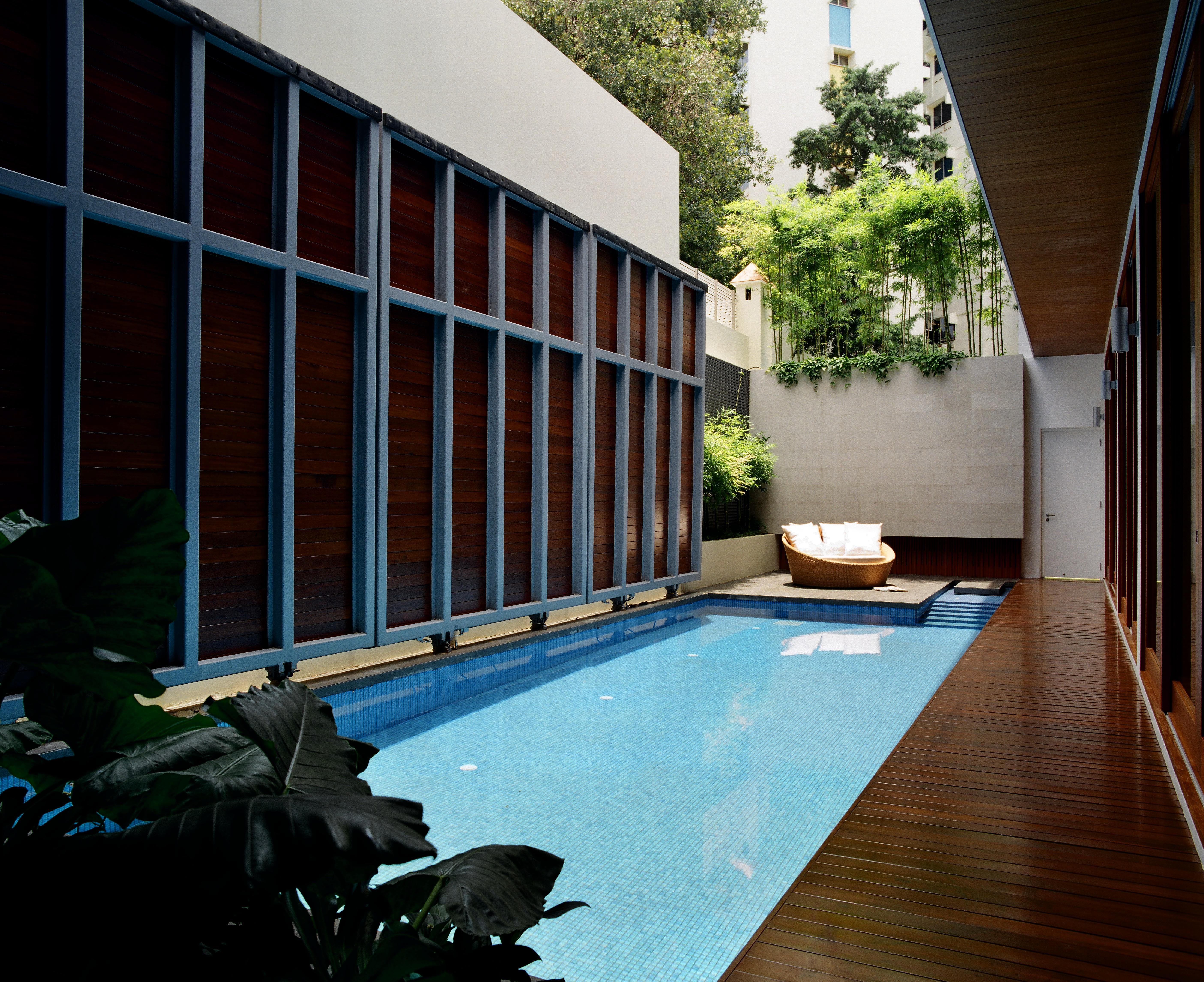 Viewed from the opposite end, we see the three immense metal and hardwood pool cover panels in the raised position, with bamboo copse standing atop brick exterior wall.
