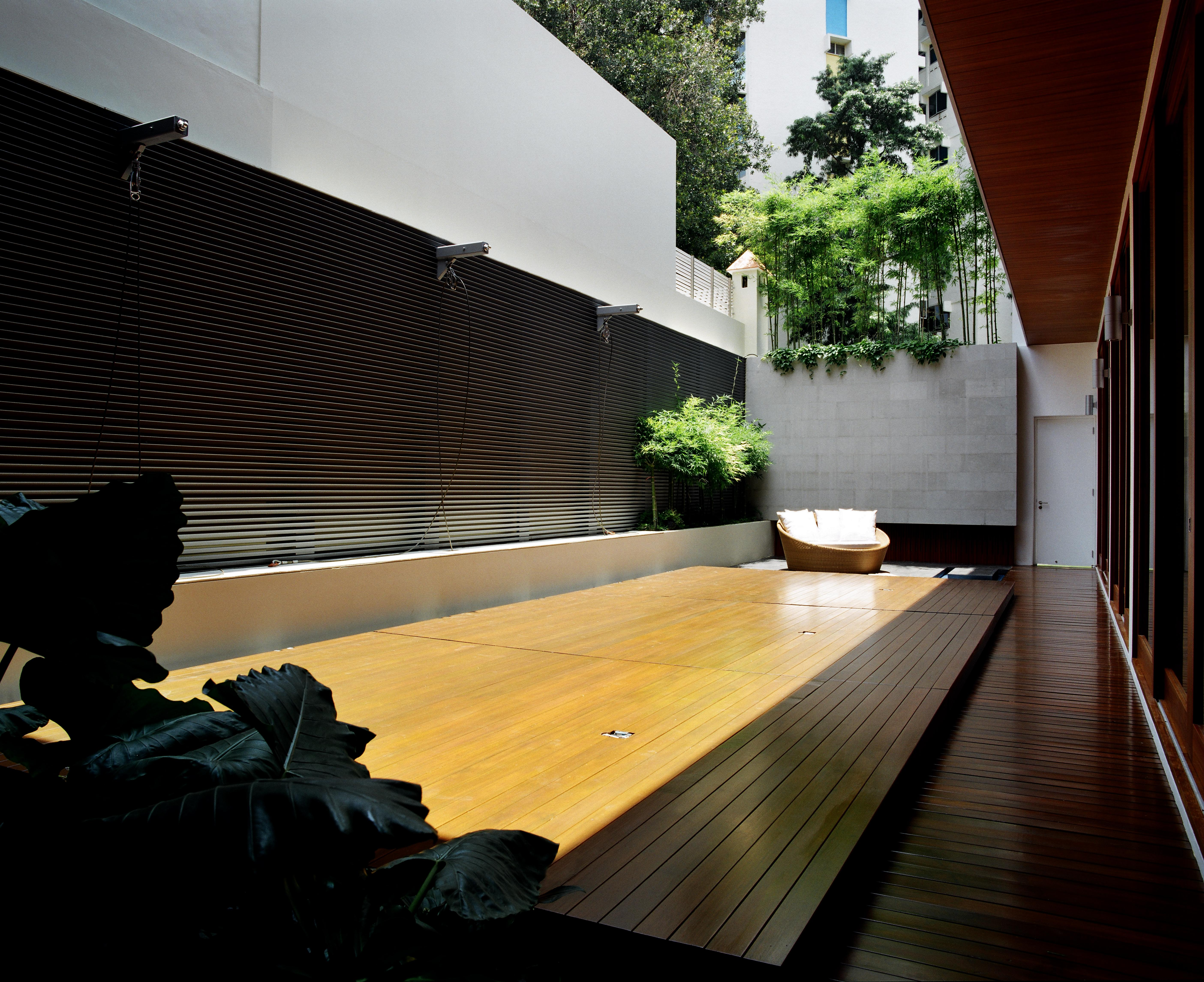 Seen in the closed position, the pool deck creates a raised hardwood platform, extending the courtyard's livable space.
