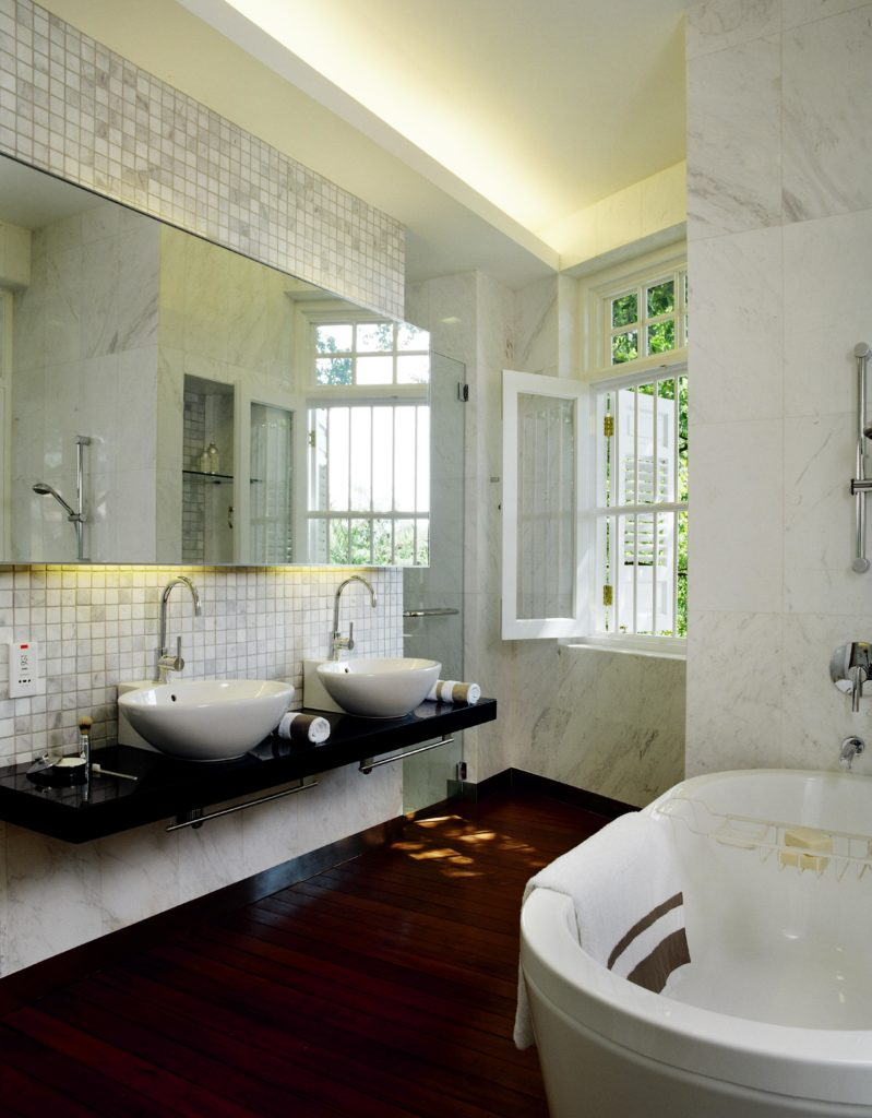 Master bath is awash in white marble walls over rich, dark hardwood flooring. Pedestal tub at right stands across from black floating vanity with a pair of vessel sinks. Glass door shower stands next to shaded white frame window.