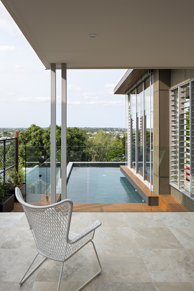 This view of the balcony reveals the layers of glass aiding the expansive views: louvered glass panel windows, sliding panels on the floor to ceiling windows, and all-glass rails surrounding the natural wood deck and pool space.