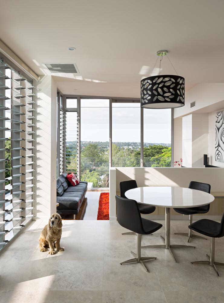 The living room space stands on rich hardwood flooring at a half lower level from the kitchen, with its beige tile flooring. Louvered and sliding glass windows all around afford expansive views and fresh air throughout.