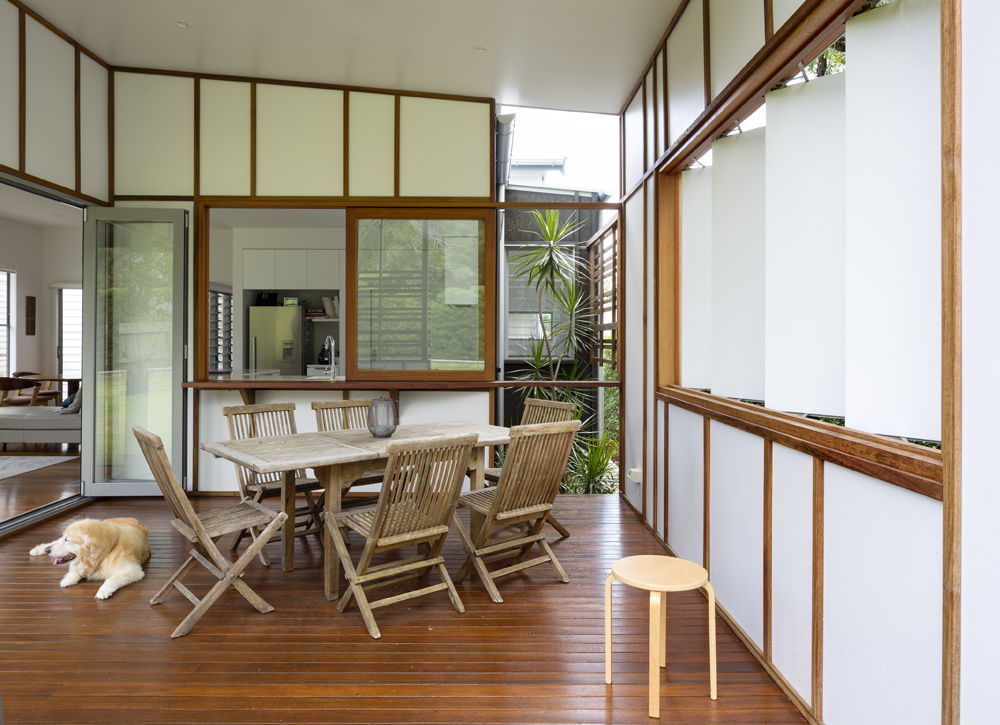 Within the patio space, we see a naturally faded wood dining set, with white louver panels at right. Kitchen is seen beyond sliding wood frame window.