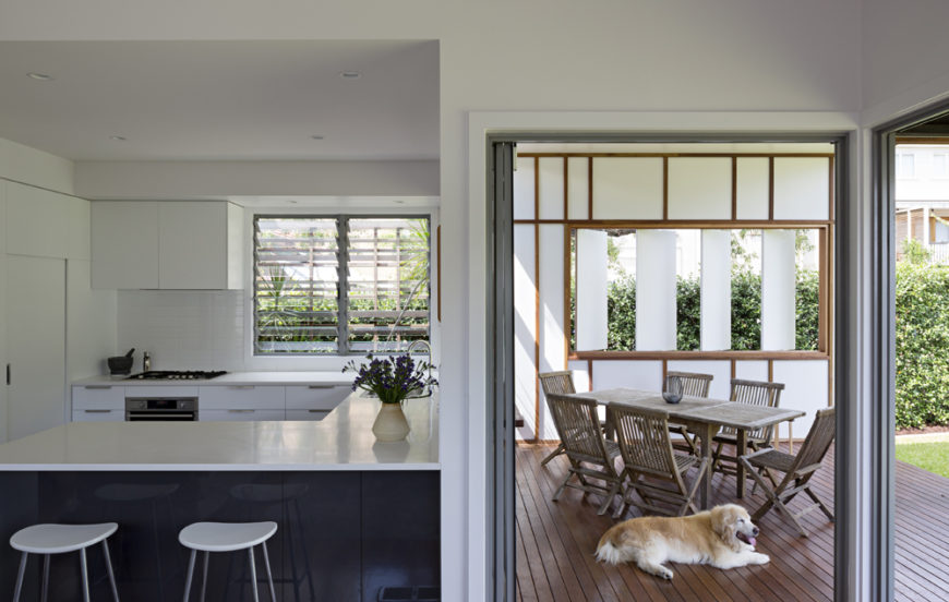 From the living room, we see an equal view of the kitchen and patio. Black wood and white countertops aid in the high contrast interior, with louvered glass windows at left, while natural wood and white panels fill the patio view.