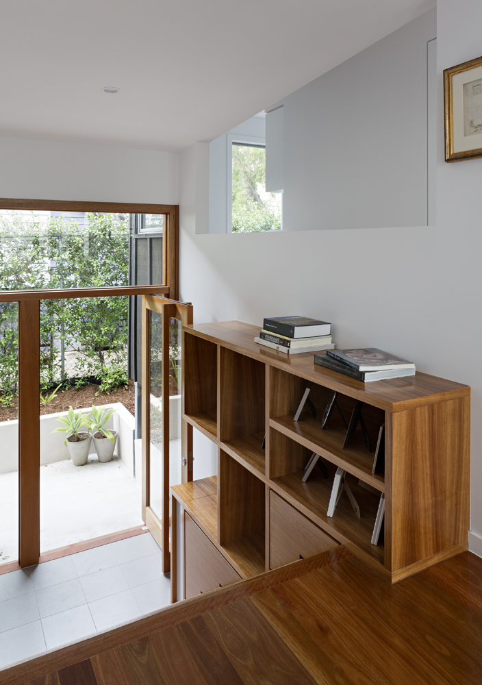 The interior features natural hardwood spread throughout, from flooring to shelving to door and window frames. This staircase features cabinetry and shelving built in, with the glass front door seen at left.