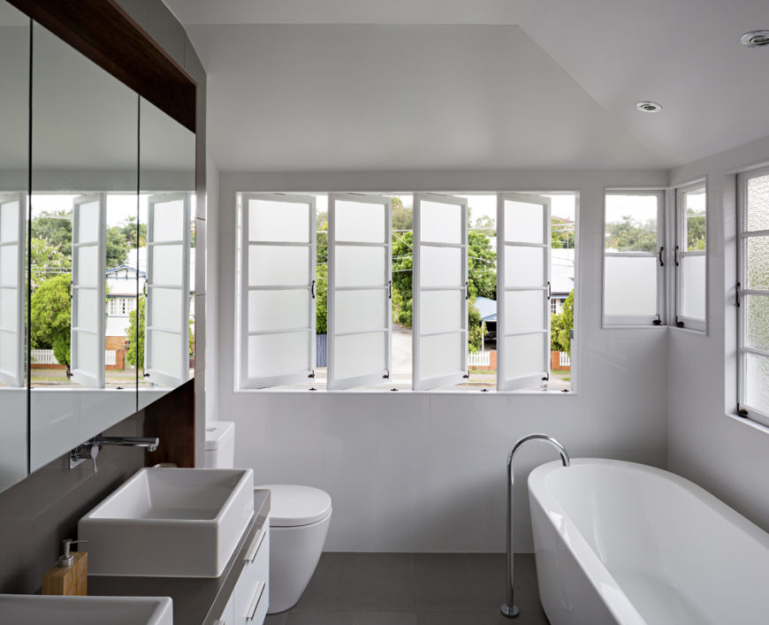 The upper floor bathroom, in grey tile and white, features a pedestal tub and dual vessel sink vanity, with another set of white louvered windows.